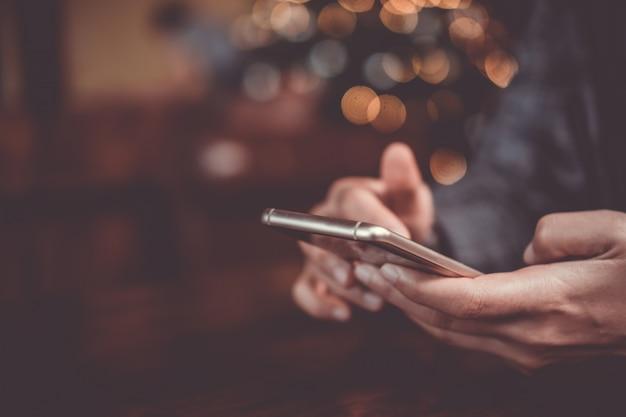 Mão de mulher usando smartphone no fundo da loja de café. negócios, financeiro, comércio de ações e rede social.