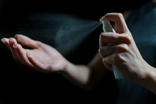 Mão de mulher usando spray desinfetante, desinfetante de álcool para parar de espalhar o coronavírus ou covid-19.