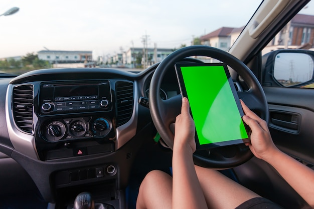Mão de mulher usando tablet com monitor de tela verde em branco no carro suv