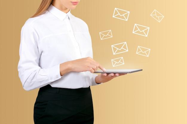 Mão de mulher usando tablet digital para enviar e receber e-mail para negócios.