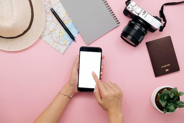 Mão de mulher usando telefone inteligente para aplainar a viagem de férias com mapa câmera e notebook.