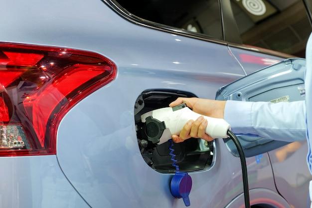 Mão de mulheres alimentando um novo veículo via máquina de eletricidade recarregável