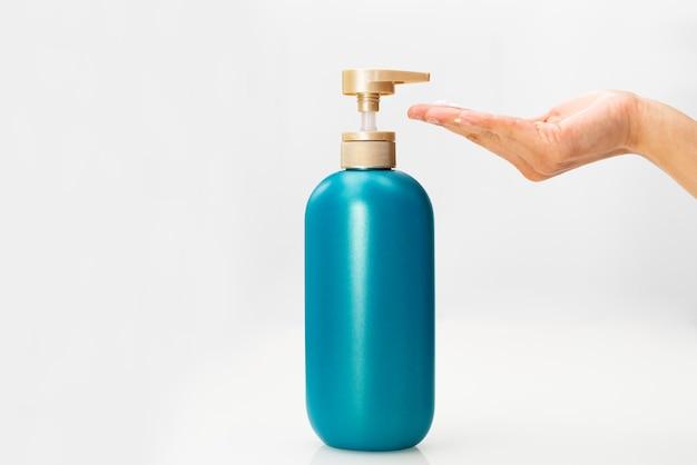 Mão de mulheres aplicar garrafa de condicionador de cabelo shampoo em branco