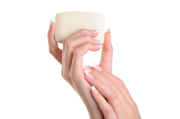 Mão de mulheres bonitas segurando o sabonete branco