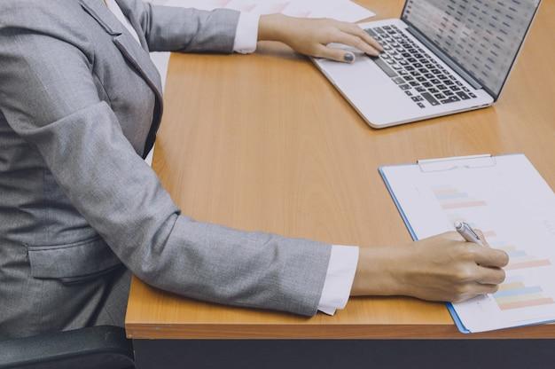 Mão de mulheres de negócios assinando no documento