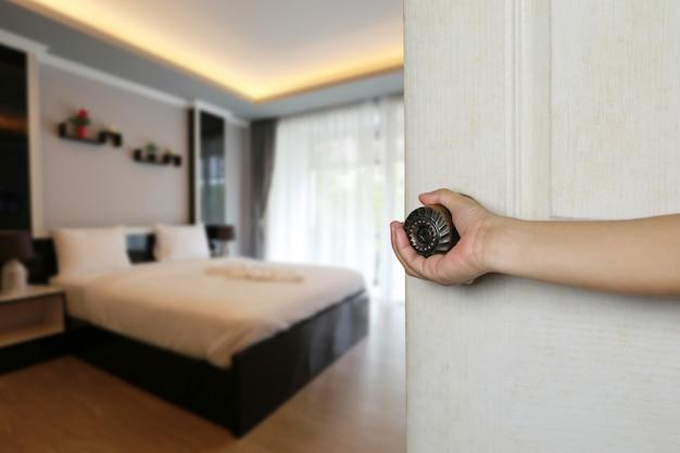 Mão de mulheres está abrindo a porta do quarto.