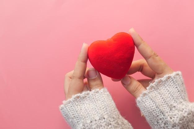 Mão de mulheres segurando um coração vermelho sobre fundo rosa.