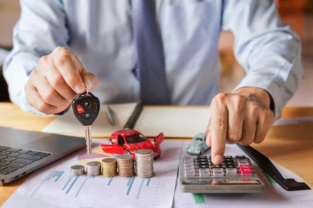 Mão de negociante de carro segurando a chave com o uso de calculadora