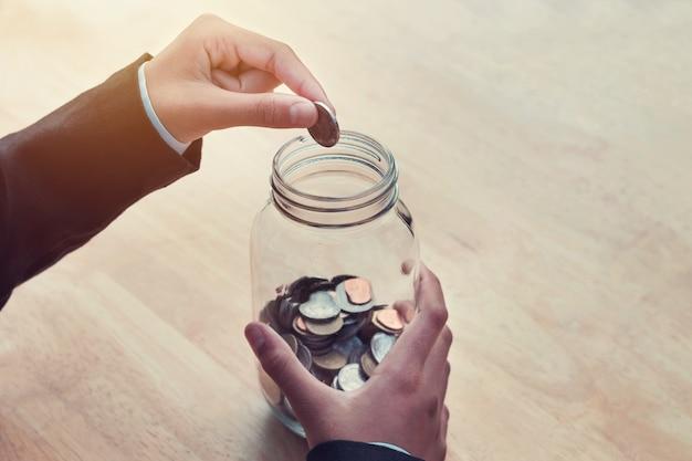 Mão de negócios colocando moedas em frasco de vidro para salvar o conceito de contabilidade de dinheiro na mesa