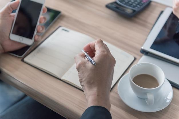 Mão de negócios com caneta anotando no caderno, outras mãos segurando o telefone.