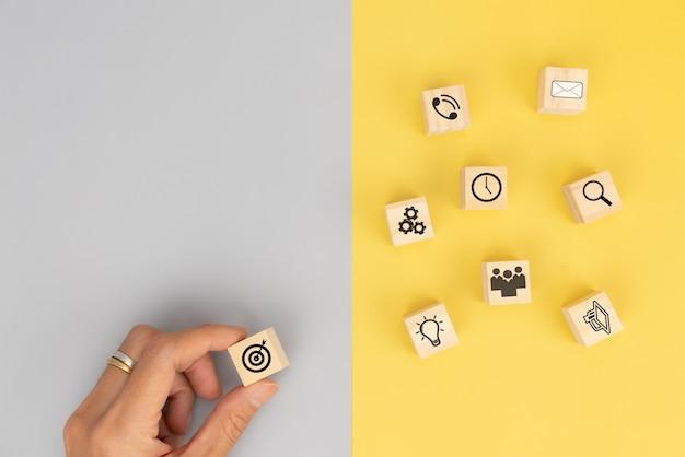 Mão de negócios organizando bloco de madeira com estratégia de negócios de ícone