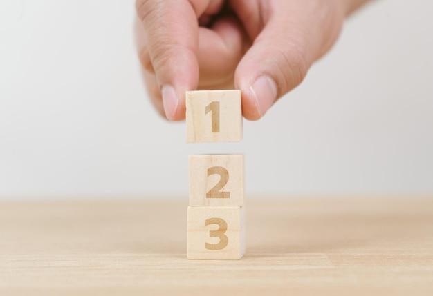 Mão de negócios, organizando o empilhamento de cubos de madeira como escada. processo de sucesso de crescimento de conceito de negócio em fundo branco, copie o espaço.