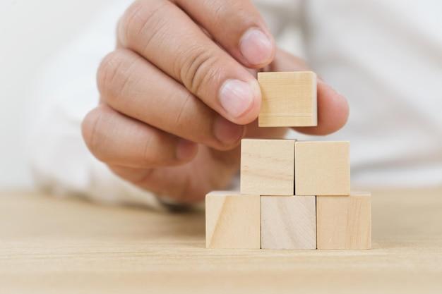 Mão de negócios, organizando o empilhamento de cubos de madeira como escada. processo de sucesso de crescimento de conceito de negócio em fundo branco