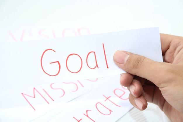 Mão de negócios segurando um pedaço de papel de meta