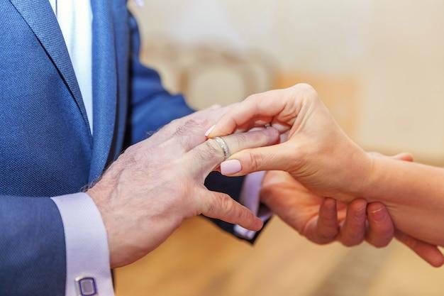 Mão de noiva colocando a aliança no dedo do noivo
