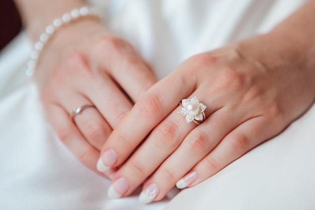 Mão de noiva com anel de diamante e pulseira de pérola no vestido branco