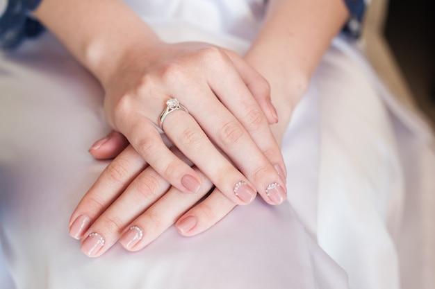 Mão de noiva com manicure no vestido de casamento