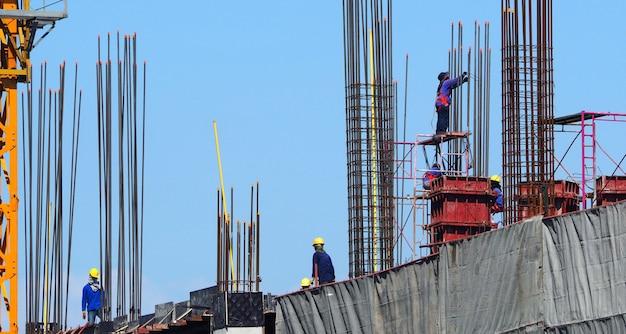 Mão de obra trabalhando em canteiro de obras que possui material industrial em prédio alto e apresenta alto risco de vida.