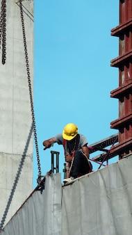 Mão de obra trabalhando no canteiro de obras e colocando vinil e aço para cobrir o prédio e o céu azul.