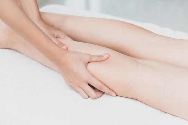 Mão de osteopata apertando massagem de perna e spa no músculo da panturrilha feminina