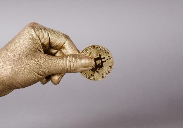 Mão de ouro detém moeda física de bitcoin cryptocurrency.