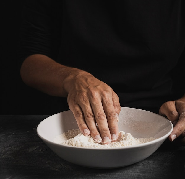 Mão de padeiro close-up, misturando a farinha