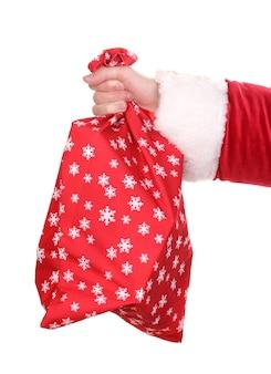 Mão de papai noel segurando um saco de presentes isolado no branco