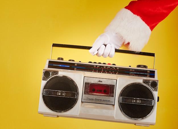 Mão de papai noel segurando um toca-fitas de rádio