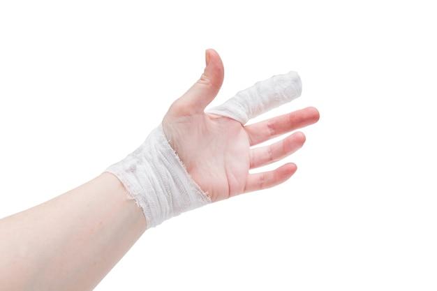 Mão de pele branca com dedo indicador e pulso enfaixados, isolado na superfície branca.