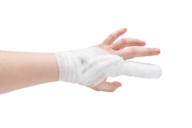 Mão de pele branca com dedo indicador e pulso enfaixados, parte traseira, isolado na superfície branca.