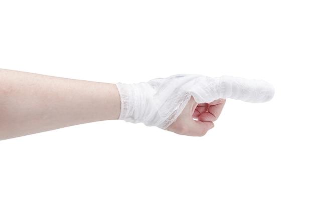 Mão de pele branca com dedo indicador enfaixado em gesto de apontar e pulso, isolado na superfície branca.