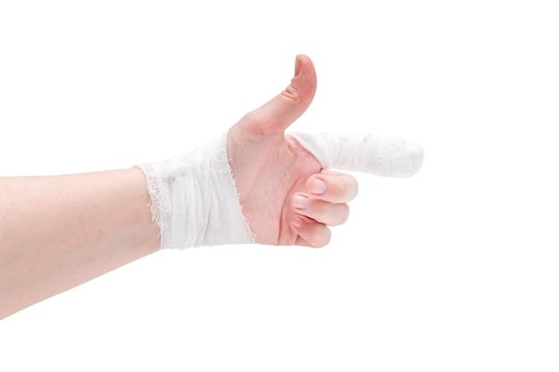 Mão de pele branca com dedo indicador enfaixado no gesto de apontar e pulso, polegar para cima, isolado na superfície branca.