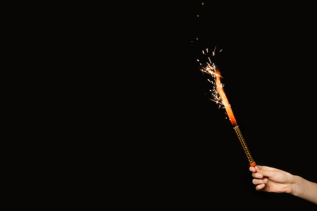 Mão de pessoa com fogo de artifício flamejante