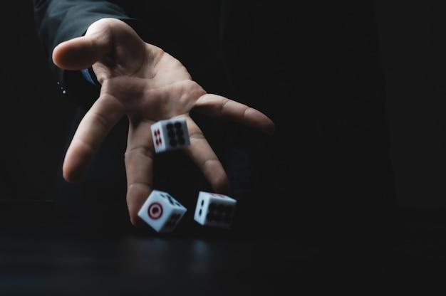 Mão de pessoa de negócios joga os dados, conceito de jogo de azar empresarial