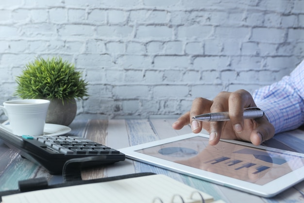 Mão de pessoa trabalhando no tablet digital, usando o gráfico criado por si,
