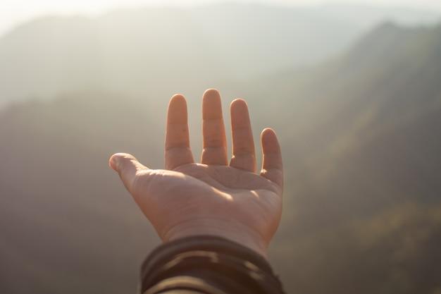 Mão de pessoas com montanha e bela vista. foco suave.