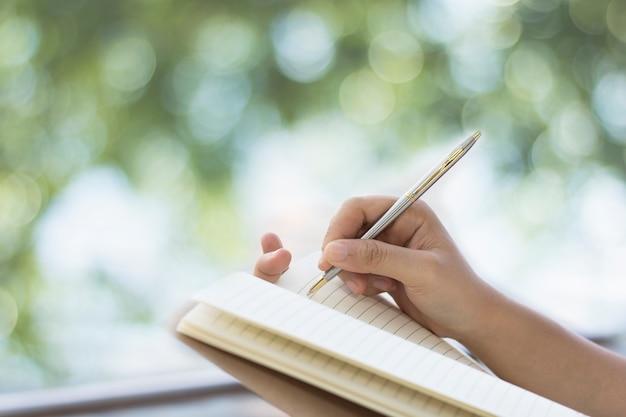 Mão de pessoas escrevendo no notebook