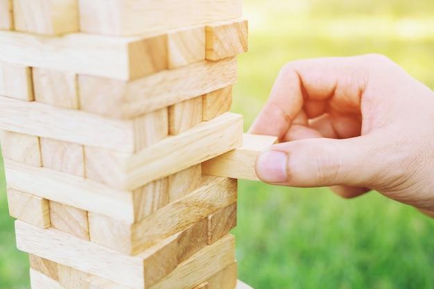 Mão de pessoas jogando pegue um jogo de pilha de blocos de madeira marrom na torre de construção. risco de planejamento de conceito e estratégia em e engenharia de construção.