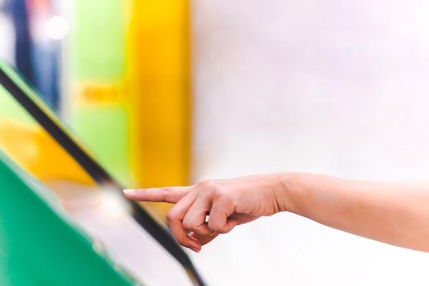 Mão de pessoas usa tela de toque digital para obter informações