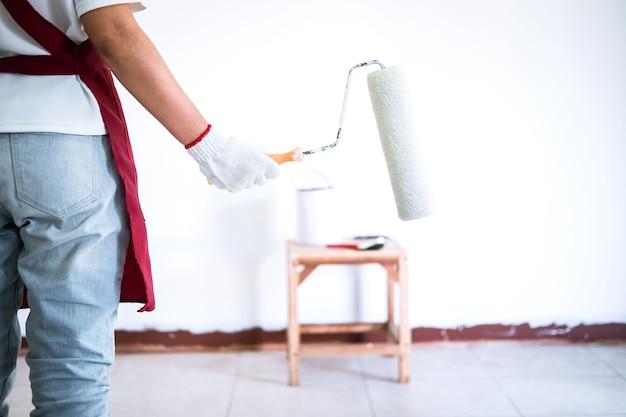 Mão de pintor na parede de pintura de luva branca com rolo de pintura na sala, forma e estrutura