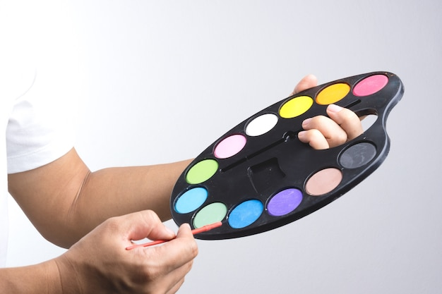 Mão de pintor segurando a placa de cor de água