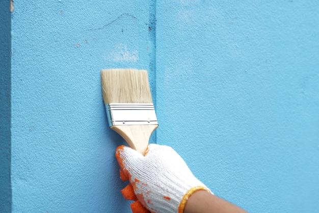 Mão de pintor segurando o ponto de pincel no alvo de trabalho na parede