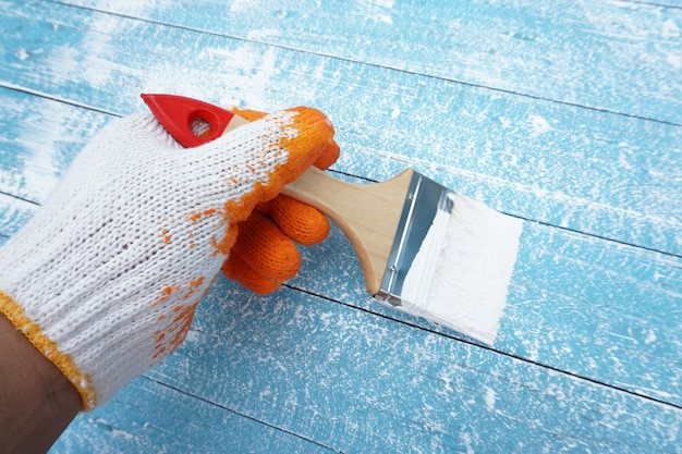 Mão de pintor segurando pincel pintar a madeira azul