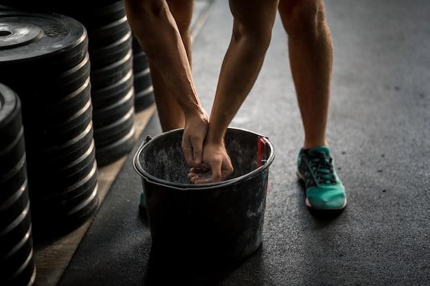 Mão de powerlifter masculino em pulseiras de talco e esportes, preparando-se para supino