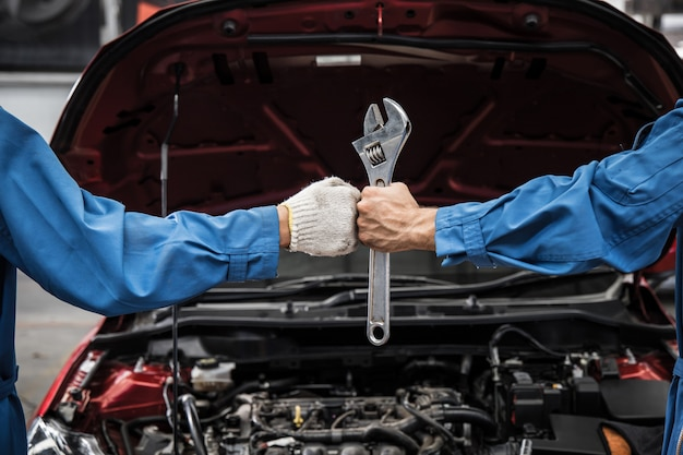 Mão de punho e mecânica com ferramenta.