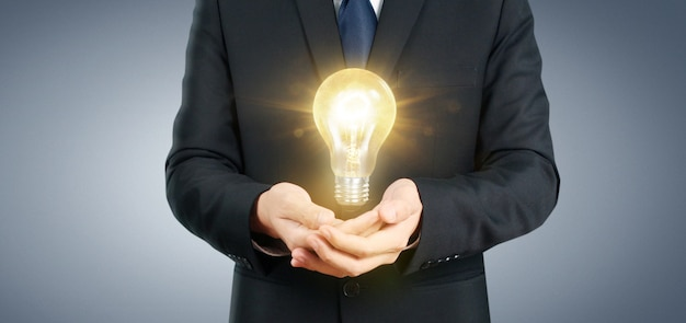 Mão de segurar a lâmpada iluminada, conceito de inspiração de inovação de idéia