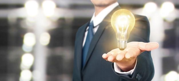 Mão de segurar a lâmpada iluminada, conceito de inspiração de inovação
