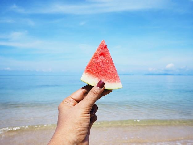 Mão de selfie que guarda a melancia sobre o fundo da praia do verão.