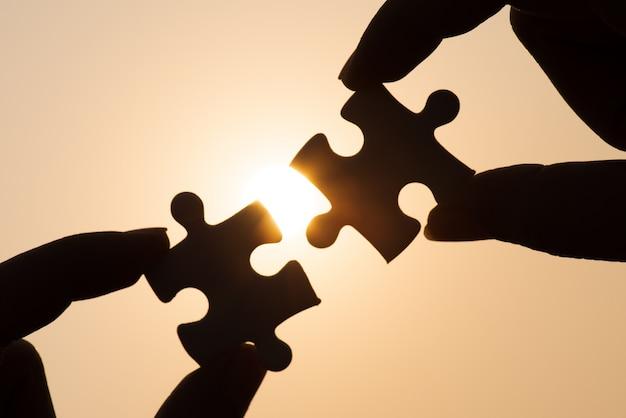 Mão de silhueta conectando um pedaço de quebra-cabeça sobre a luz solar, estratégia de negócios.