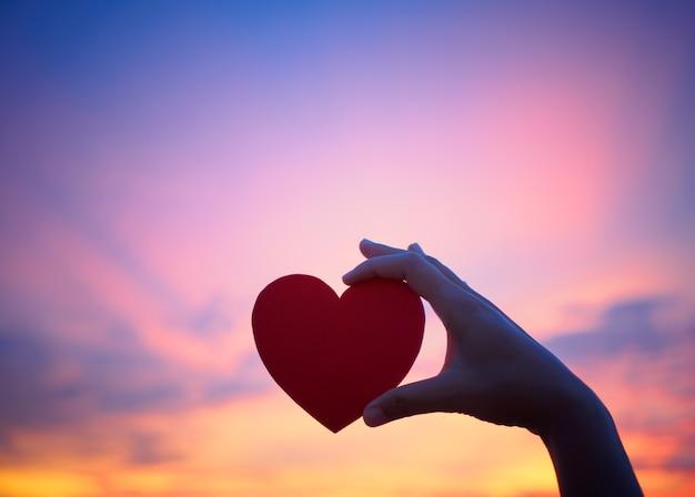 Mão de silhueta segurando coração lindo durante o fundo por do sol